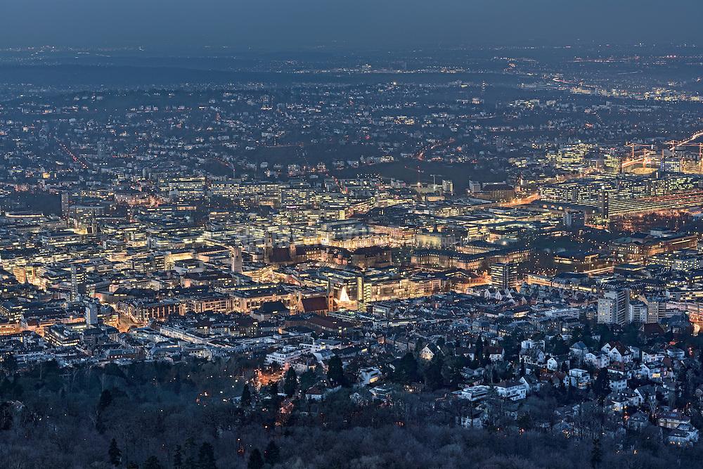 Blick vom Fernsehturm auf Stuttgart bei Dämmerung mit umliegendem Wald