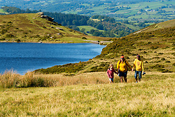 © Licensed to London News Pictures. 18/09/2020.  Builth Wells, Powys, Wales, UK. As the heatwave continues in Wales a family walk near a lake on the Mynydd Epynt moorlad near Builth Wells in Powys, UK. Photo credit: Graham M. Lawrence/LNP