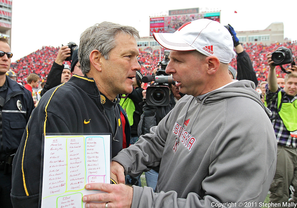 November 25, 2011: Iowa Hawkeyes head coach Kirk Ferentz and Nebraska Cornhuskers head coach Bo Pelini greet each other after the end of the NCAA football game between the Iowa Hawkeyes and the Nebraska Cornhuskers at Memorial Stadium in Lincoln, Nebraska on Friday, November 25, 2011. Nebraska defeated Iowa 20-7.