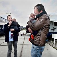 Nederland, Amsterdam , 1 oktober 2014.<br /> De rij caravans met mensen die een zelfbouwkavel willen kopen op het Zeeburgereiland wordt steeds groter.<br /> Sommige staan al een paar weken in de wachtrij totdat ze een kavel mogen kopen. Pas volgende week zaterdag gaan de kavels pas in de verkoop, maar wie weg gaat, verliest zijn plek in de rij.<br /> Een van de kampeerders staat er al een tijdje in zijn caravan: 'Ik ben hier behoorlijk vroeg gaan staan, want er is &eacute;&eacute;n kavel waar ik echt ge&iuml;ntresseerd in ben. Er hoeft er maar een eerder te zijn en dan ben je 'm kwijt.'<br /> De wachtende kopers vinden het best gezellig op het terrein: 'Je ontmoet een soort van je toekomstige buren als het zo doorgaat. Dat geeft een apart campinggevoel en we barbecuen samen.'<br /> Een probleempje, als je weggaat ben je je plek kwijt. 'Als je moet werken moet je zorgen dat er iemand anders op je plek zit. Ik had hier eerst helemaal geen zin in, maar het is toch wel een bizar avontuur.'<br /> Op de foto: 2 kavelkopers en hun kinderen.<br /> Foto:Jean-Pierre Jans