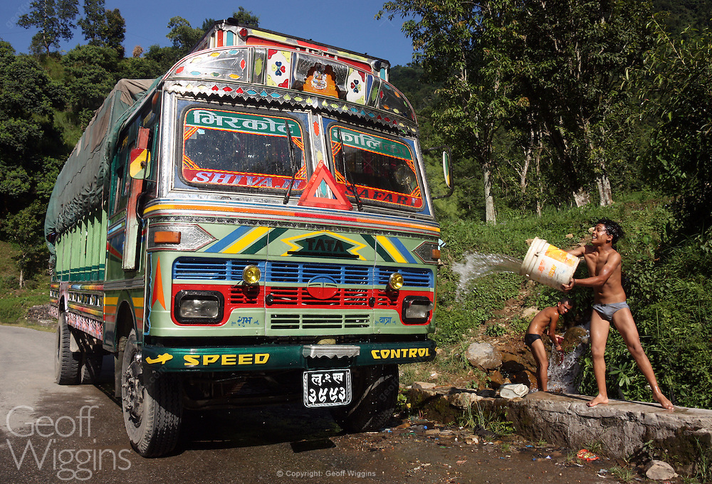 Young co driver washes decorated Nepali Tata 1613 truck at mountaln stream, Jagatpur, Nepal,
