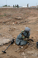 A SPLA deminer clearing a huge number of unexploded ordinance found scattered across a large, open terrain just opposite John Garang's tomb in Juba as the area was being prepared for South Sudan independence ceremonies. The Government of South Sudan called on Mines Advisory Group (MAG) to assist SPLA deminers in an attempt to clear the area and make it safe for the thousands of people and dignitaries who will be attending the declaration of independence on July 9th...Juba, South Sudan. 04/07/2011..Photo © J.B. Russell