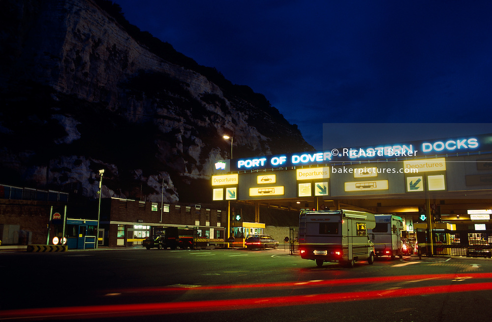 As darkness approaches, a queue of campervans and other vehicles queue up at the first checkpoint in the Port of Dover's Eastern Docks, the holidaymakers' first step to travelling across the English Channel to France or Belgium. beneath the famous white cliffs of Dover, that symbol of England's edge that is seen from the sea as one leaves or approaches the English shores. It is dusk and the flood lights have started illuminating the busy port roads and ramps, the red rear tail lights from a truck cross the picture's foreground and the signs - with graphics of busses, cars  and arrows that tell drivers in which lane to line-up glow yellow. Dover has long been one of the World's premier seaports, with centuries of maritime heritage, presented with a Royal Charter in 1606.