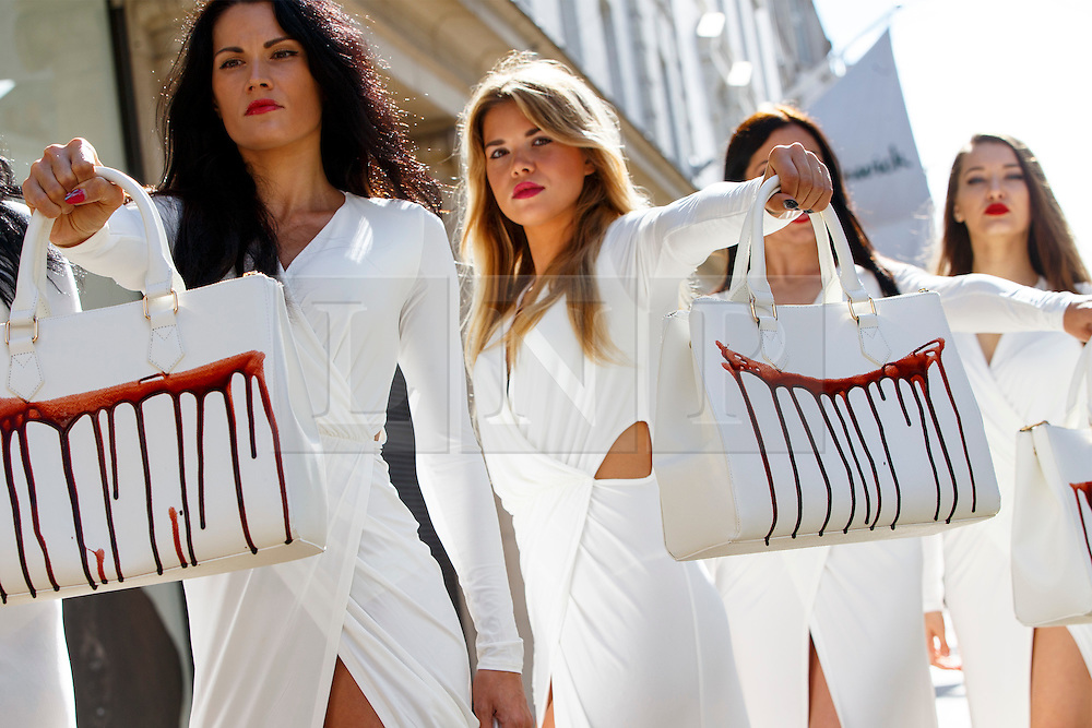 © Licensed to London News Pictures. 17/09/2015. London, UK. PETA models holding brandishing handbags covered in fake blood to protest against the use of animal skins in London Fashion Week on Thursday, 17 September 2015 in central London. Photo credit: Tolga Akmen/LNP