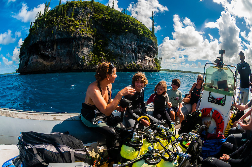 Scuba divers in a zodiac with Easo cliffs in background, Lifou (island), Loyalty Islands, New Caledonia