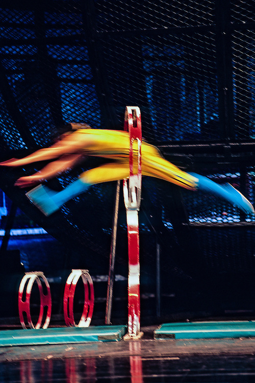 One of Shanghai's world famous acrobats jumps through a hoop several feet off of the ground.