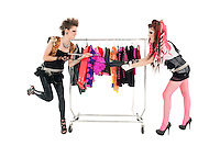 Punk women pulling dress in front of clothes rack over white background