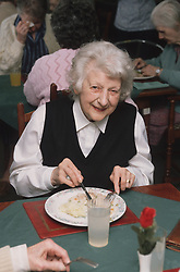 Elderly woman eating meal in residential home,