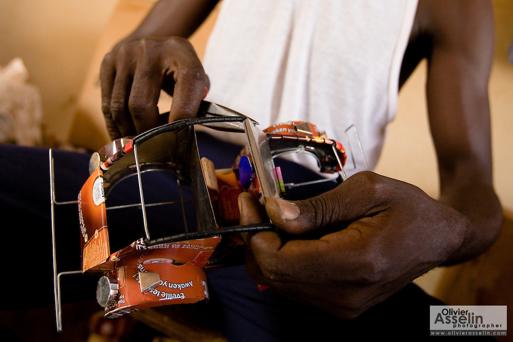 A man makes cars from recycled metal cans at the Village Artisanal de Ouagadougou, a cooperative that employs dozens of artisans who work in different mediums, in Ouagadougou, Burkina Faso, on Monday November 3, 2008.