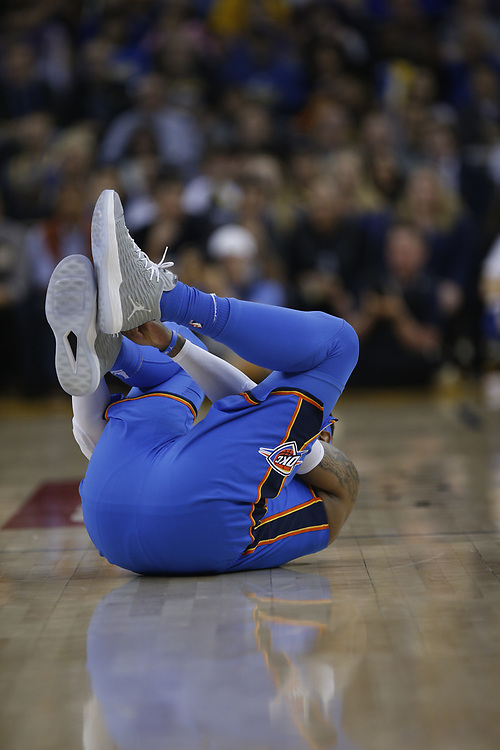Oklahoma City Thunder forward Carmelo Anthony (7) injury his ankle during the first half of an NBA game between the Golden State Warriors and Thunder at Oracle Arena, Tuesday, Feb. 6, 2018, in Oakland, Calif. Anthony later left the game with a sprained right ankle.
