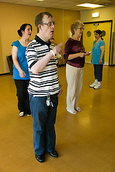 Day Service users with learning disability taking part in dance class with Day Care Officer and Care Assistant joining in the activity,