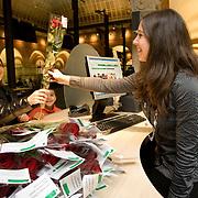 Nederland Rotterdam 6 april 2009 20090406 Foto: David Rozing ..Medewerker Publiekszaken overhandigt bezoeker een rode roos, in het kader van landelijke actiedag tegen agressie en geweld. Beeld is deels ge-ensceneerd, handeling laten herhalen. ..Foto David Rozing