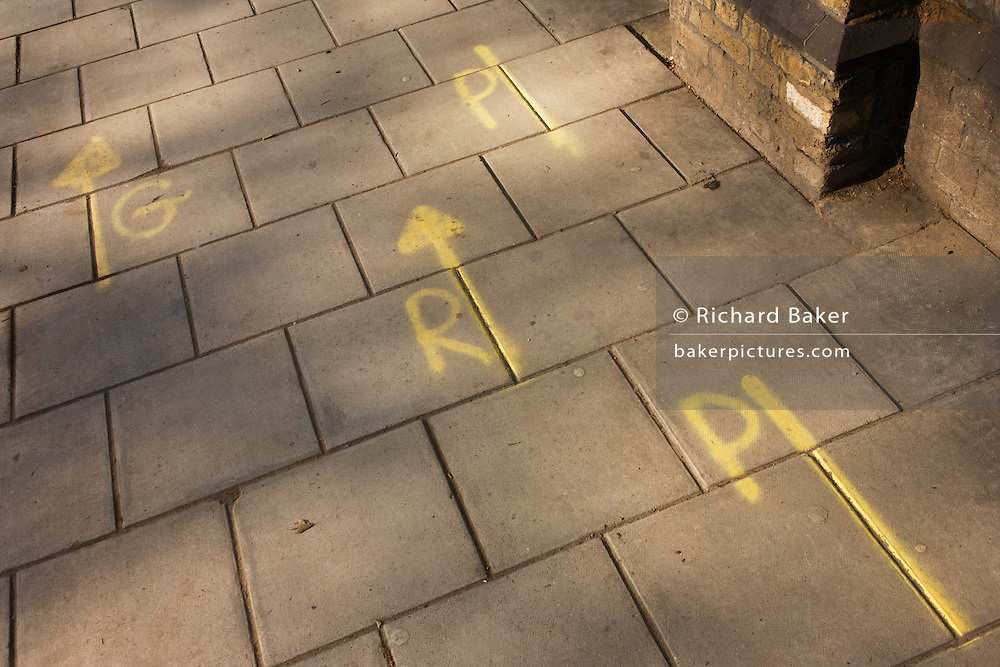 Oddly coloured letters sprayed on to a city pavement (sidewalk), perhaps of a coded meaning or technical message.