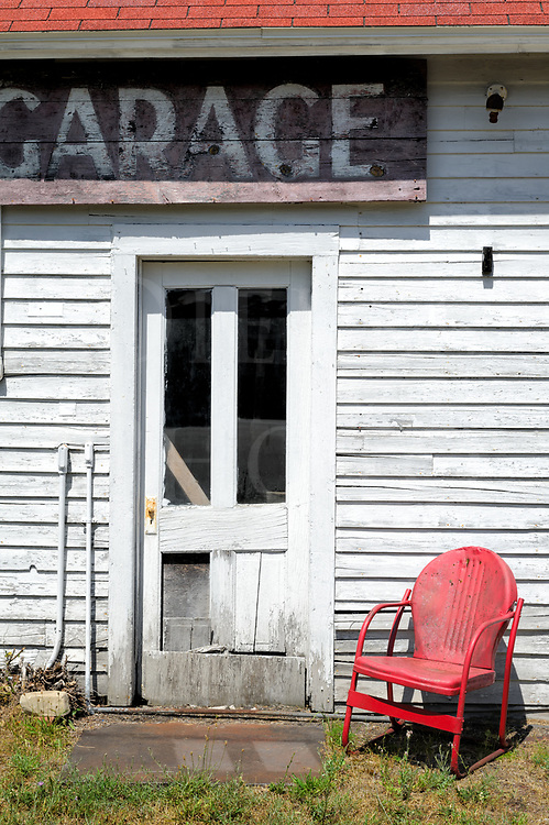 An old metal chair sitting in the bright summer sun is sure to be a hot seat for anyone wanting to rest there, but it appears no one is about to come around this closed down garage.