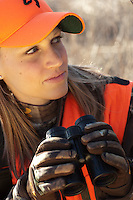 DEER HUNTER WEARING BLAZE ORANGE GLASSING FOR DEER WITH BINOCULARS
