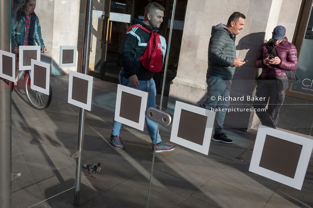 Londoners and squares on the glass screens at a bus stop in Kingston, on 7th November 2019, in London, England