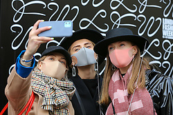 © Licensed to London News Pictures. 14/02/2020. London, UK. Fashion enthusiasts wearing fashionable face masks take a selfie as they arrive for the London Fashion Week shows in The Strand. The latest Coronavirus patient in London is linked to 'super spreader'attended transport conference with 250 people in Westminster. Photo credit: Dinendra Haria/LNP
