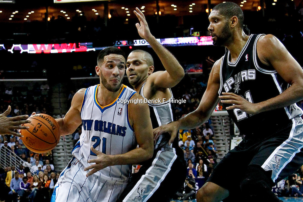 October 31, 2012; New Orleans, LA, USA; New Orleans Hornets point guard Greivis Vasquez (21) drives past San Antonio Spurs point guard Tony Parker (9) and power forward Tim Duncan (21) during the second quarter of a game at the New Orleans Arena. Mandatory Credit: Derick E. Hingle-US PRESSWIRE