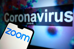 The Zoom logo seen displayed on a mobile phone with an illustrative model of the Coronavirus displayed on a monitor in the background. Photo credit should read: James Warwick/EMPICS Entertainment