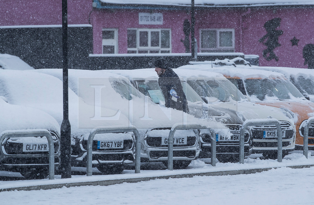© Licensed to London News Pictures. 27/02/2018. New Hythe, UK.  A man attempts to clear snow from a line of cars on a garage forecourt as snow continues to fall. Freezing temperatures and heavy snow are affecting large parts of Kent.  Photo credit: Peter Macdiarmid/LNP