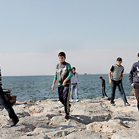 Young men walk on rocks along the coast of Izmir, Turkey.