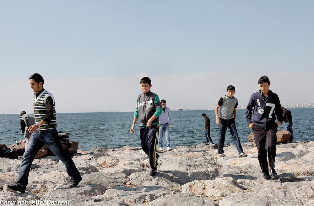 Young men walk on rocks along the coast of Izmir, Turkey.
