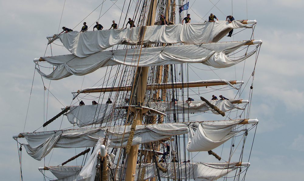 Crew members furl the sails on the US Coast Guard Cutter Eagle when it arrives at Fort Trumbull, New London, Connecticut at the conclusion of the Parade of Sail on Day 2 of OpSail 2012. The Eagle, originally a German ship, came to the US as part of war reparations after WWII. The 295-foot barque, now a training ship for the United States Coast Guard, led the parade of tall ships.