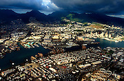 The island of Oahu has a very active port area not far from downtown and the mountains behind.