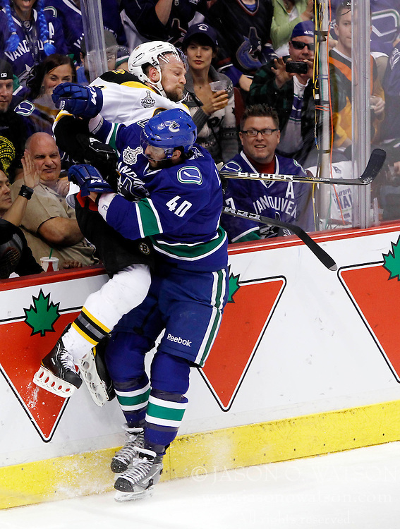 June 4, 2011; Vancouver, BC, CANADA; Vancouver Canucks right wing Maxim Lapierre (40) checks Boston Bruins defenseman Dennis Seidenberg during the first period in game two of the 2011 Stanley Cup Finals at Rogers Arena. Mandatory Credit: Jason O. Watson / US PRESSWIRE