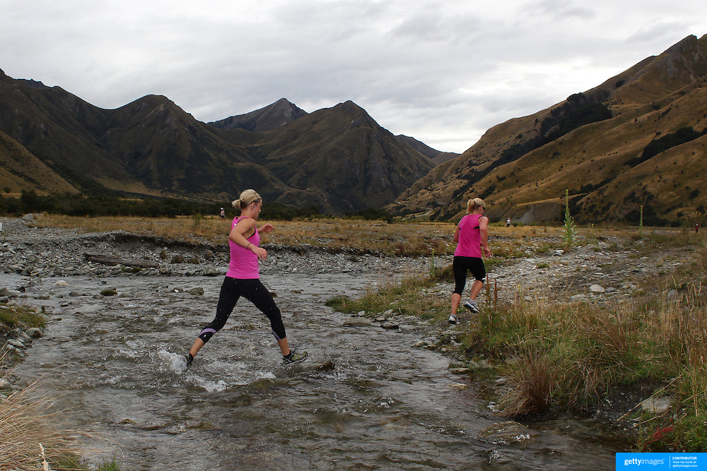 Runners crosses  Moke Creek on the Ben Lomond High Country Station during the Pure South Shotover Moonlight Mountain Marathon and trail runs. Moke Lake, Queenstown, New Zealand. 4th February 2012. Photo Tim Clayton