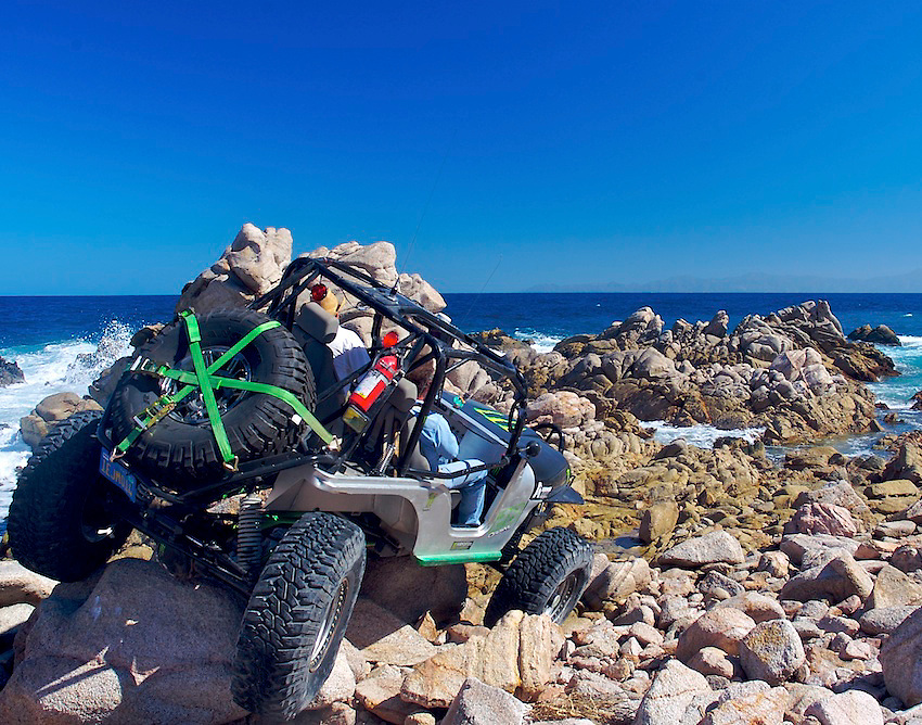Bart Dixon creeps his four wheel steering Jeep CJ over beach rocks in Baja, Mexico.