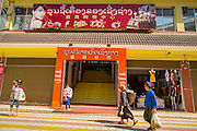 12 MARCH 2013 - ALONG HIGHWAY 13, LAOS: Hmong women walk past the entrance to the Chinese department and grocery store in the Chinese market in Oudomaxy. The Chinese market in Oudomaxy is still under construction but much of the market is empty. Oudomaxy has a large Chinese immigrant community. By some estimates, as much as 40% of the people now living in the town are originally from China, most from the province Yunnan in southern China. The paving of Highway 13 from Vientiane to near the Chinese border has changed the way of life in rural Laos. Villagers near Luang Prabang used to have to take unreliable boats that took three hours round trip to get from the homes to the tourist center of Luang Prabang, now they take a 40 minute round trip bus ride. North of Luang Prabang, paving the highway has been an opportunity for China to use Laos as a transshipping point. Chinese merchandise now goes through Laos to Thailand where it's put on Thai trains and taken to the deep water port east of Bangkok. The Chinese have also expanded their economic empire into Laos. Chinese hotels and businesses are common in northern Laos and in some cities, like Oudomxay, are now up to 40% percent. As the roads are paved, more people move away from their traditional homes in the mountains of Laos and crowd the side of the road living off tourists' and truck drivers.    PHOTO BY JACK KURTZ