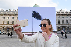 """© Licensed to London News Pictures. 20/04/2017. London, UK. A woman takes a selfie at the unveiling at Somerset House of """"Western Flag"""" (Spindletop, Texas) 2017 by artist John Gerrard.  The artwork, in the form of an LED wall installation, is a symbol for climate change and modern society's dependence on oil and has been commissioned by Channel 4 as part of their Man-Made Planet season to mark this year's Earth Day (22nd April).   Photo credit : Stephen Chung/LNP"""