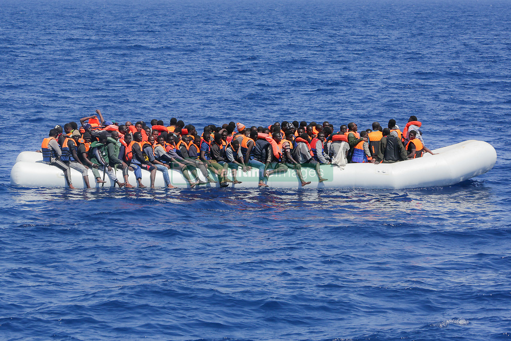 May 19, 2017 - Lampedusa, Sicily, Italy - LAMPEDUSA, ITALY - MAY 19: Refugees and migrants are seen floating in an overcrowded rubber boat as they wait to be assisted by search and rescue crew members from NGO Sea-Eye on May 18, 2017 in international waters off the coast of Libya. (Credit Image: © Christian Marquardt/NurPhoto via ZUMA Press)