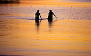 A couple wades during sunset at Lake Megunticook Camden Maine