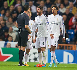 MADRID, SPAIN - Tuesday, November 4, 2014: Real Madrid's Sergio Ramos is shown a yellow card during the UEFA Champions League Group B match against Liverpool at the Estadio Santiago Bernabeu. (Pic by David Rawcliffe/Propaganda)
