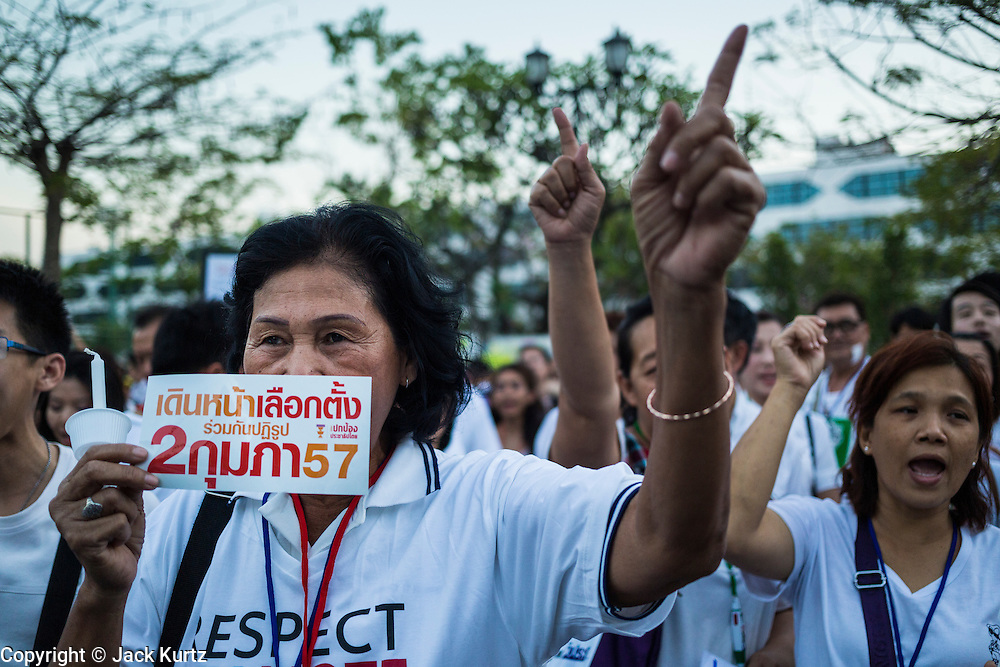 "12 JANUARY 2014 - BANGKOK, THAILAND: Women carry stickers supporting the February 2 election in Thailand. About 500 people from all walks of Thai life came to a candlelight vigil at Thammasat University. They prayed for a peaceful resolution to the political conflict in Thailand. They finished the vigil by singing the John Lennon song ""Imagine."" Anti-government protestors are expected ""Shutdown Bangkok"" Monday. There were reports Sunday evening that some intersections were already being blocked.       PHOTO BY JACK KURTZ"