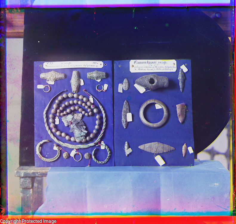 1905<br /> Tver is an ancient city (first mentioned in 1135) on the Volga River to the northwest of Moscow. Opened in 1866, the Tver Museum displayed natural and archeological items of interest as well as works of art and crafts from the region of Tver. Seen here are arrowheads and other stone implements (on right), as well as jewelry, such as rings, bronze bracelets, and necklaces. The items, clearly labeled, are from the Ostashkov and Zubtsov regions. In 1897 the museum was allocated space in the Imperial Transit Palace. Nationalized in 1918, the museum was given the entire Transit Palace in 1921, where it remained until World War II. During the German occupation of Tver in the fall of 1941 the museum was severely damaged, resulting in the loss of most of its holdings. The image is by Russian photographer Sergei Mikhailovich Prokudin-Gorskii (1863&ndash;1944), who used a special color photography process to create a visual record of the Russian Empire in the early 20th century. Some of Prokudin-Gorskii&rsquo;s photographs date from about 1905, but the bulk of his work is from between 1909 and 1915, when, with the support of Tsar Nicholas II and the Ministry of Transportation, he undertook extended trips through many different parts of the empire. In 1910 his work included photographing a number of exhibits in the Tver Museum.