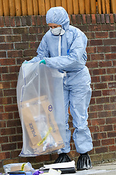 © Licensed to London News Pictures. 31/03/2019. London, UK. A Forensic Officer collects the victim's belongings on Fore Street in Edmonton, north London where a person was stabbed just after 9.30am this morning. The victim was taken to a hospital by Air Ambulance and his condition is unknown. Photo credit: Dinendra Haria/LNP