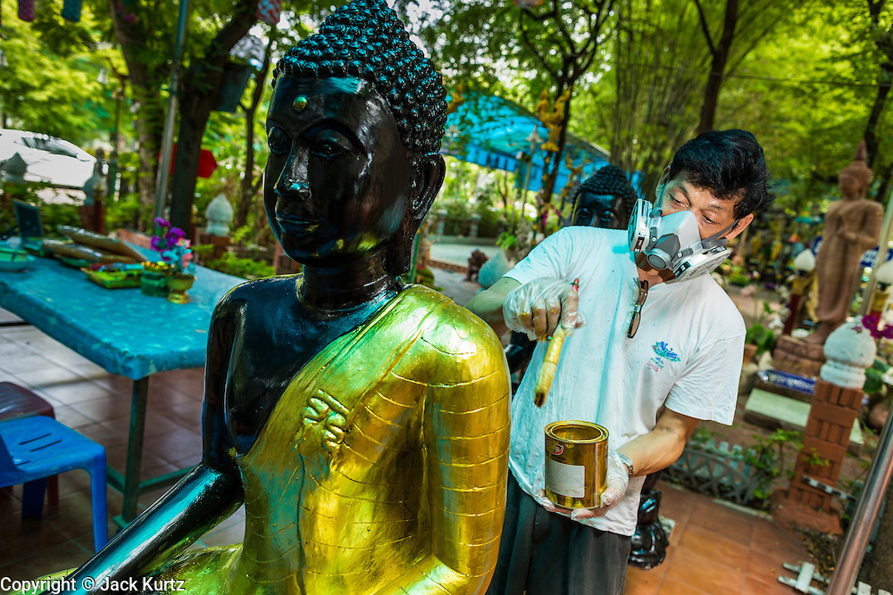 15 JULY 2014 - BANGKOK, THAILAND:   A worker at Wat Rachathiwat Ratchaworawihan on Samsen Soi 9 paints a statue of the Buddha. The temple has a large teak instruction hall, considered one of the finest teak buildings in Asia.   PHOTO BY JACK KURTZ