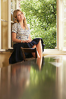 Young woman sitting on window sill in living room