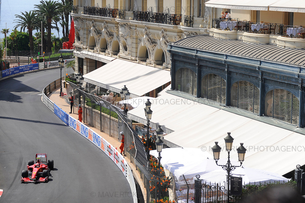 Cars pound around the streets of Monte Carlo during Thursday practice ahead of this weekends Monaco Grand Prix.  Pictured spectators watch on from their hotel balcony as Ferrari driver Kimi Raikkonen makes his way around the Casino Square section of the circuit.