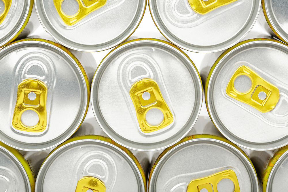 Aluminium drink cans with gold ring pulls stacked on top of each other