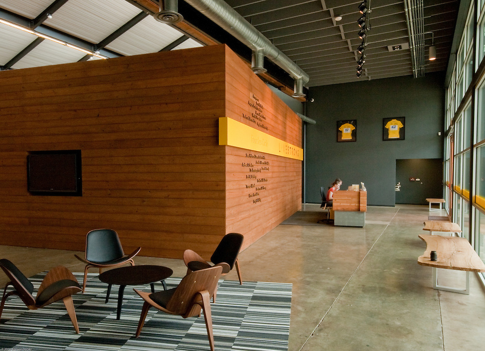 An iconic yellow stripe boldly accents the donor wall in the lobby of the Lance Armstrong Foundation offices.