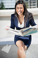 Portrait of a laughing Indian businesswoman with newspaper sitting outdoors