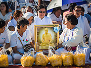 """02 JANUARY 2016 - KHLONG LUANG, PATHUM THANI, THAILAND:  People look at picture of the Abbot of Wat Phra Dhammakaya and pray while they wait for the start of a mass pilgrimage of Buddhist monks at Wat Phra Dhammakaya on the first day of the 5th annual Dhammachai Dhutanaga (a dhutanga is a """"wandering"""" and translated as pilgrimage). More than 1,300 monks are participating pilgrimage through central Thailand. The purpose of the pilgrimage is to pay homage to the Buddha, preserve Buddhist culture, welcome the new year, and """"develop virtuous Buddhist youth leaders."""" Wat Phra Dhammakaya is the largest Buddhist temple in Thailand and the center of the Dhammakaya movement, a Buddhist sect founded in the 1970s. The monks are using busses on some parts of the pilgrimage this year after complaints about traffic jams caused by the monks walking along main highways.         PHOTO BY JACK KURTZ"""