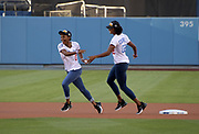 Jun 13, 2018; Los Angeles, CA, USA; Anna Cockrell (2) hands a baseball off to Deanna Hill (3) during a ceremonial relay before a MLB game between the Texas Rangers and the Los Angeles Dodgers at Dodger Stadium. Constantine and Cockrell ran the first and second legs of the Southern California Trojans women's 4 x 400m relay that won the NCAA title in the final even to win  the national team title.