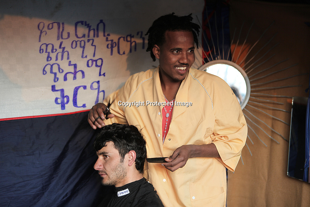 Illegal immigrants from Sudan giving a hair cut to an Afghan man. They are living in an abandoned basketball gym in Calais, France. They hope to reach UK illegaly by jump on a truck and get on the ferry to Dover.