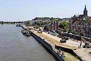 Nederland, Nijmegen, 8-7-2013Werkzaamheden om de damwand van de Waalkade te vervangen. De damwand die de kade tegenhoudt is  aan het verzakken. De waterkering wordt ondergraven door wegspoelend zand. Hij is uit positie en dus instabiel. De kade is afgezet en er mogen geen schepen aanlegen. De waterkering dateert van 1980, 1981. Ook het drukke scheepvaartverkeer op de Waal zorgt voor een zware belasting.Foto: Flip Franssen