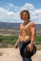 muscular tan cowboy outdoors on a mountain range
